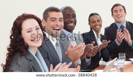 Happy business team laughing and clapping in a meeting - stock photo