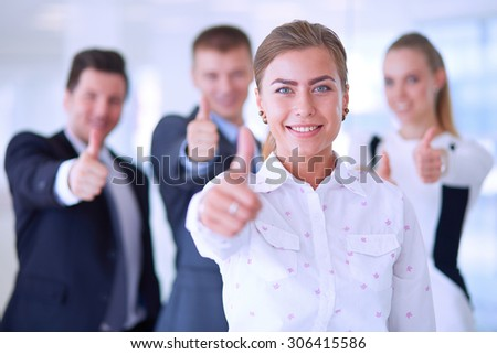 Happy business team showing thumbs up in office . - stock photo