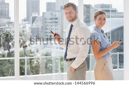 Happy business team standing back to back and texting by large windows - stock photo