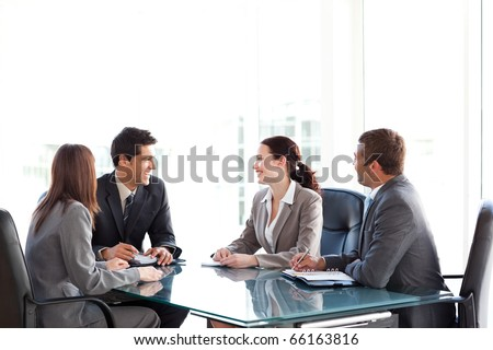 Happy business team talking together during a meeting sitting at a table - stock photo