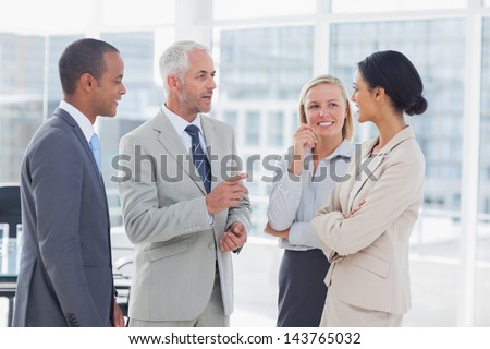 Happy business team talking together in the office - stock photo