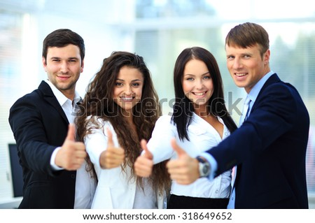 Happy business team with thumbs up in the office - stock photo