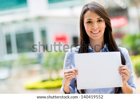 Happy business woman holding a banner and smiling - stock photo