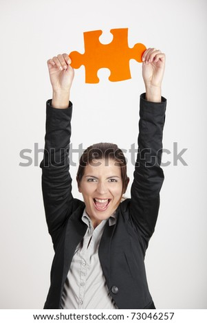 Happy business woman holding a big piece of puzzle, isolated on white