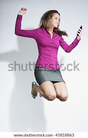 happy business woman holding cellphone and jumping for joy. Copy space - stock photo