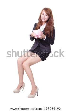 Happy business woman holding pink piggy bank and sitting on something isolated against white background, asian beauty - stock photo