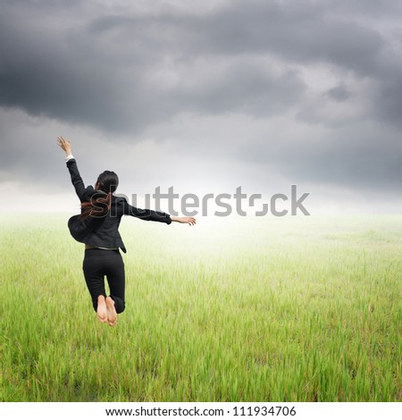 Happy Business woman jumping to raincloud in grassland - stock photo