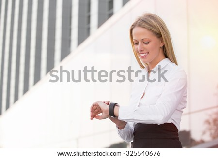 Happy business woman looking at her smartwatch - stock photo