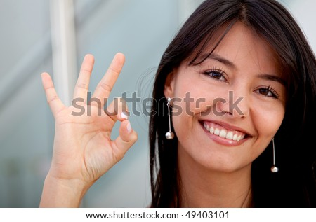 Happy business woman making an ok sign - stock photo