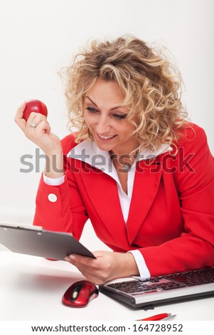 Happy business woman or office worker reading a memo sitting by her desk - stock photo