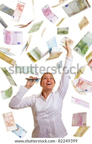Happy business woman reaching for raining money - stock photo