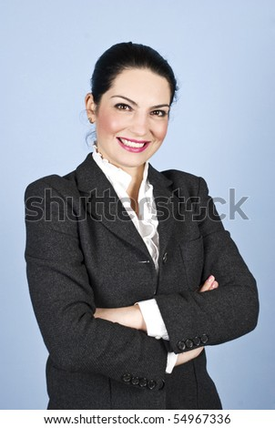 Happy  business woman 30s standing with arms folded  and smiling in front of blue background - stock photo
