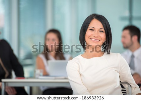 Happy business woman sitting in modern office