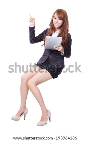 Happy business woman sitting on something and using tablet pc isolated against white background, asian beauty - stock photo