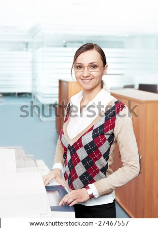 happy business woman standing near copier in modern office environment - stock photo