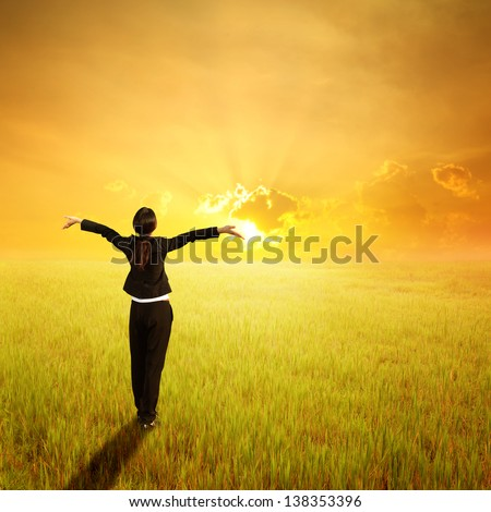 Happy Business woman standing to sunset in grassland