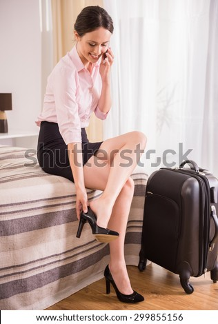 Happy business woman talking by phone and taking down her shoes while sitting on bed near suitcase at the hotel room. - stock photo