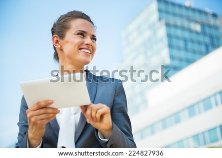 Happy business woman using tablet pc in front of office building - stock photo