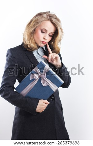 Happy business woman with a gift. Portrait of a blonde in a jacket on a white.woman showing copyspace or something - stock photo