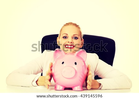 Happy business woman with a piggybank behind the desk - stock photo