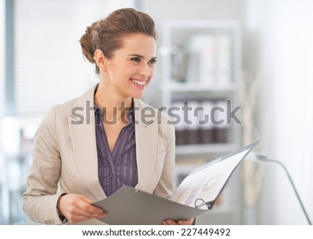 Happy business woman with documents in office - stock photo