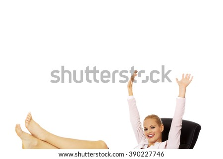 Happy business woman with hands up holding legs on the desk - stock photo