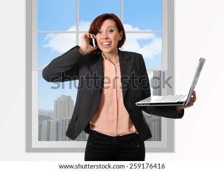 Happy business woman with red hair talking on the mobile cell phone holding computer laptop in hand multitasking excited in front of business district office window view - stock photo