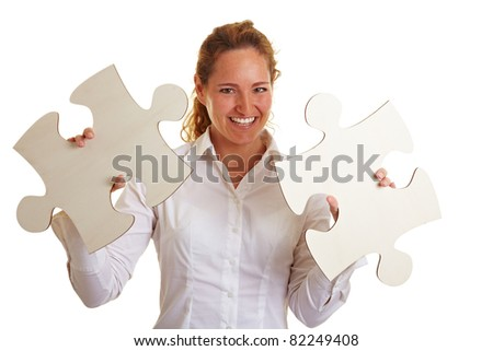 Happy business woman with two oversized jigsaw pieces - stock photo