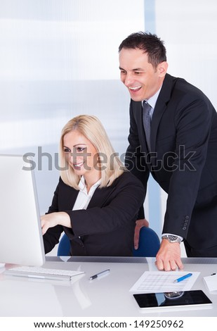 Happy Businessman And Businesswoman Looking At Computer - stock photo