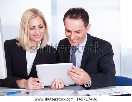 Happy Businessman And Businesswoman Looking At Digital Tablet - stock photo