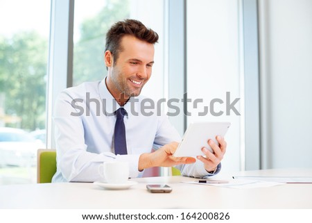 Happy businessman browsing web on digital tablet in the office - stock photo