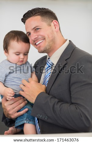 Happy businessman carrying baby boy while looking away at home - stock photo