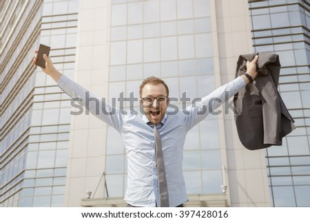 Happy businessman celebrating his success in front of the business building  - stock photo