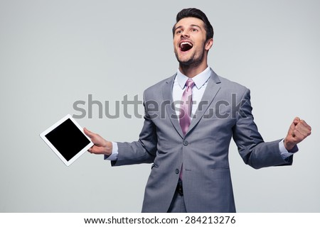 Happy businessman celebrating his success over gray background - stock photo