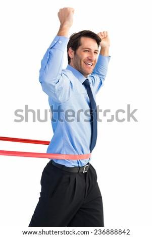 Happy businessman crossing finishing line on white background - stock photo