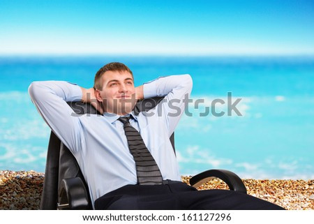 Happy businessman dreaming about vacation sitting in a chair - stock photo