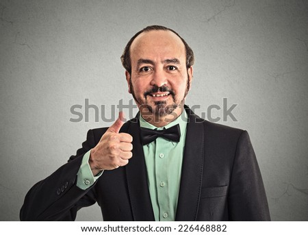 Happy businessman giving showing thumbs up sign hand gesture isolated on grey wall office background. Positive emotion face expression body language attitude  - stock photo
