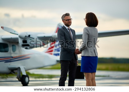 Happy businessman handshaking with his partner on background of airplane  - stock photo