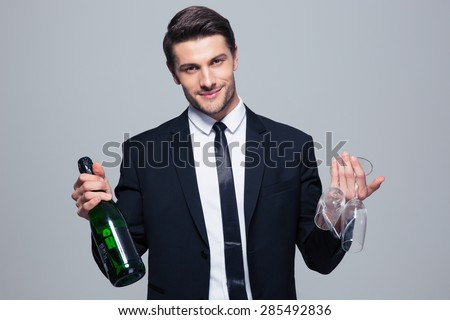 Happy businessman holding bottle with champagne and glass over gray background - stock photo