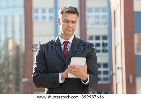 Happy Businessman Holding Digital Tablet Outside Office Building