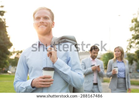 Happy businessman holding disposable cup with colleagues standing in background - stock photo