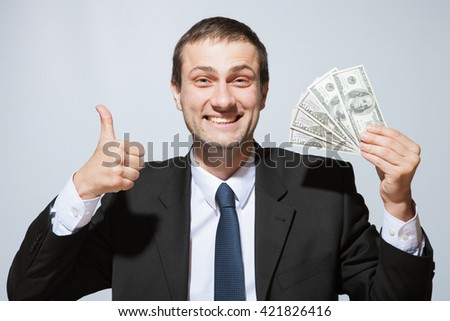 Happy businessman holding dollars and showing thumb up sign, neutral background