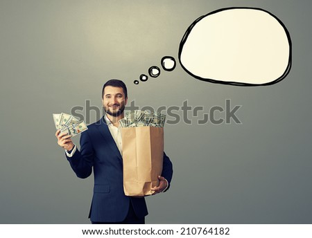 happy businessman holding paper bag and money with drawing speech empty bubble over grey background - stock photo