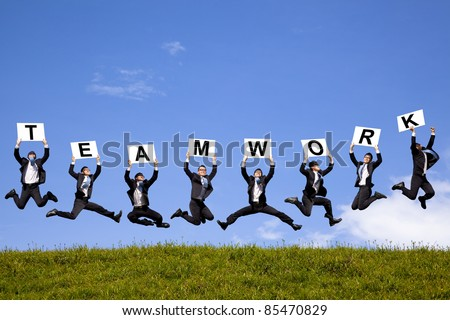 happy businessman holding teamwork text and jumping on the green field - stock photo