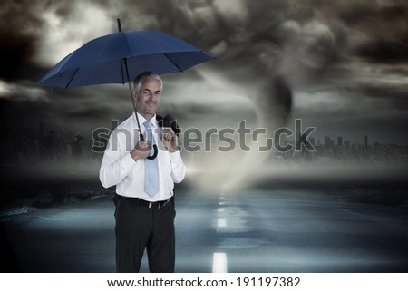 Happy businessman holding umbrella against stormy sky with tornado over road