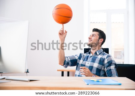 Happy businessman in casual cloth sitting at the table and spinning ball in office - stock photo