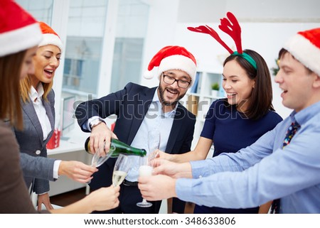 Happy businessman in Santa cap pouring champagne into flutes of his colleagues in office