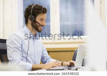 Happy Businessman in the office on the phone, headset, Skype - stock photo