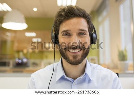Happy Businessman in the office on the phone, headset, Skype. looking camera - stock photo