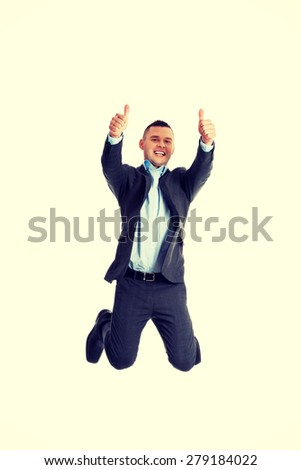 Happy businessman jumping in the air with thumbs up - stock photo